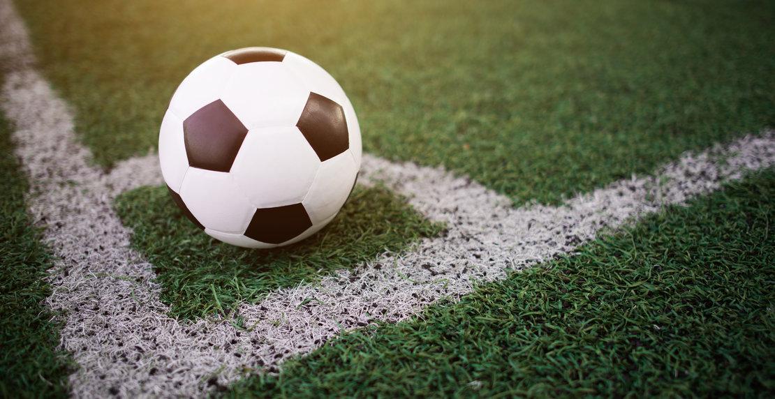 soccer ball on the white line at stadium